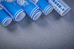 Rolls dei disegni di ingegneria blu sul constructi grigio del fondo Fotografia Stock