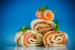 Rolls dei pancake sottili con il pesce rosso salato Fotografia Stock