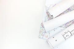 Rolls dei piani della costruzione e l'utilizzazione del territorio del progetto proiettano su bianco immagine stock libera da diritti