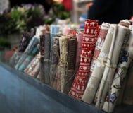Rolls dei vestiti multicolori limitati da un pezzo di corda in scatola di cartone fotografia stock
