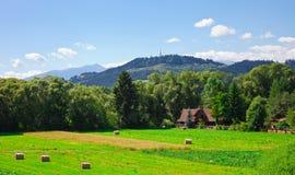 Rolls del heno inclinado en el campo y la pequeña casa rural Fotografía de archivo libre de regalías