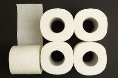 Rolls del papel higiénico blanco en un fondo negro, concepto foto de archivo libre de regalías