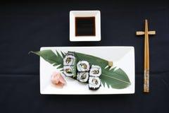Rolls del sushi con el nori del arroz seeweed y de pescados en una placa blanca con los palillos del hashi foto de archivo