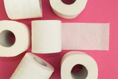 Rolls della carta igienica bianca su un fondo rosa fotografia stock libera da diritti