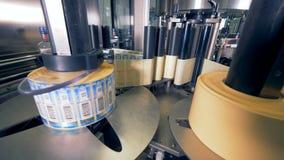 Rolls delle etichette per le bottiglie Lo speciale che la macchina fila, mettendo etichetta sulle bottiglie in una pianta archivi video