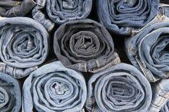 Rolls der unterschiedlichen getragenen Blue Jeans gestapelt Stockfotografie