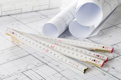 Rolls des plans architecturaux de construction de logements de modèle avec la règle de pliage photos libres de droits