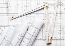 Rolls des plans architecturaux de construction de logements de modèle sur le fond de modèle s'étendent à plat avec la règle de pl photo stock