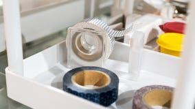 Rolls des rubans avec les modèles mignons dans le support de distributeur dessus Photos stock