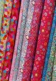 Rolls des tissus imprimés colorés Images libres de droits