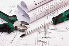 Rolls of diagrams and work tools on electrical construction drawing of house Royalty Free Stock Photography