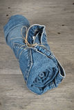Rolls of different worn blue jeans stacked Stock Photo