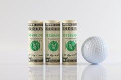 Rolls of dollar bills and golff ball Stock Photo