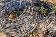 Rolls dos cabos pretos da telecomunicação que encontram-se na terra foto de stock