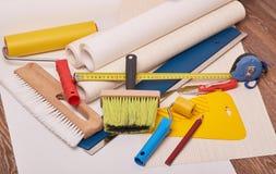 Rolls dos papéis de parede e de várias ferramentas para wallpapering fotos de stock