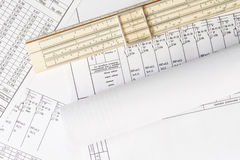 Rolls of drawings and slide rule on the scheme Stock Photography