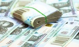 Rolls e os pacotes de naira descontam moedas locais em um montão da pirâmide imagens de stock royalty free