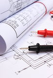 Rolls of electrical diagrams and cables of multimeter on drawing of house Stock Images