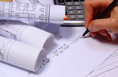 Rolls of electrical diagrams, calculator and mathematical calculations Stock Photo