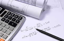 Rolls of electrical diagrams, calculator and mathematical calculations. For project, drawings for the projects engineer jobs royalty free stock photos