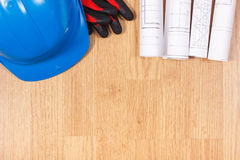 Rolls of electrical drawings, protective blue helmet and gloves, accessories for engineer jobs Stock Photo