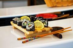 Rolls et sushi dans les plats traditionnels sur la table dans le restaurant asiatique photographie stock libre de droits