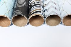 Rolls of festive wrapping paper and space for text on white background, closeup. Gift box packaging. Ideas stock images