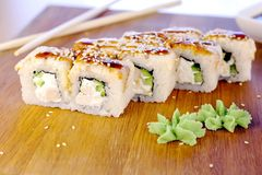 Rolls with fish and sesame seed on top served in wooden board with wasabi, ginger and soy sause. Rolls with fish and sesame seed on top served in wooden board stock photos