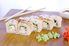Rolls with fish and sesame seed on top served in wooden board with wasabi, ginger and soy sause. Rolls with fish and sesame seed on top served in wooden board stock image