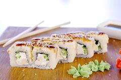 Rolls with fish and sesame seed on top served in wooden board with wasabi, ginger and soy sause. Rolls with fish and sesame seed on top served in wooden board stock photo