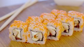 Rolls with fish, shrimps and orange caviar on top served on wooden board, close-up view. Rolls with fish, shrimps and orange caviar on top served on wooden stock video footage