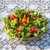 Rolls från aubergine- och grönsallatsidor som dekorerades med blommor, klippte från körsbärsröda tomater på en bästa sikt för vit Arkivbild