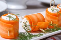 Rolls of fresh carrots with cheese and dill macro. Rolls of fresh carrots with soft cheese and dill on white plate macro. horizontal Stock Images