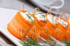 Rolls of fresh carrots with soft cheese on the table Stock Image