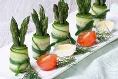 Rolls of fresh cucumber with green asparagus on a plate. With quail eggs and tomatoes. horizontal Stock Photography