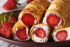 Rolls with fresh strawberries and cream cheese macro. Rolls with fresh strawberries and cream cheese on a plate macro. horizontal Stock Image