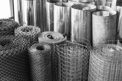 Rolls of galvanized metal sheets, steel chicken wire mesh, and p. Lastic wire mesh, material for making divider royalty free stock photo