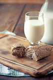 Rolls with a glass of milk. On wooden table Stock Photography