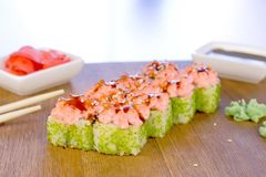Rolls with green caviar and sauce on top on wooden board with with wasabi, ginger and soy sause. Rolls with green caviar and sauce on top on wooden board with stock photo