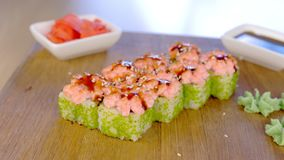Rolls with green caviar and sauce on top on wooden board with with wasabi, ginger and soy sause. Rolls with green caviar and sauce on top on wooden board with stock video