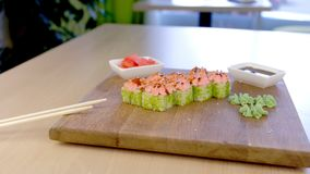 Rolls with green caviar and sauce on top on wooden board with with wasabi, ginger and soy sause on the table in cafe. Rolls with green caviar and sauce on top stock video