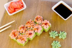 Rolls with green caviar and sauce on top on wooden board with with wasabi, ginger and soy sause, top view. Rolls with green caviar and sauce on top on wooden royalty free stock photography