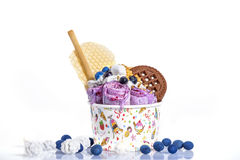 Rolls of ice cream with cookies and colorful decoration in a paper cup against a white background Stock Photos