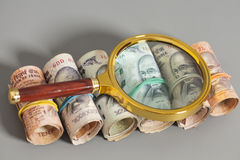 Rolls of Indian Currency Rupee Notes with magnifying glass on gr Stock Images