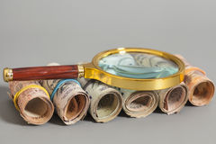 Rolls of Indian Currency Rupee Notes with magnifying glass on gr Stock Photography