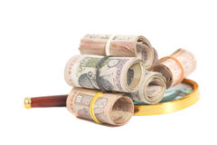 Rolls of Indian Currency Rupee Notes with magnifying glass Stock Photo
