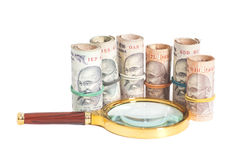 Rolls of Indian Currency Rupee Notes with magnifying glass Stock Photography