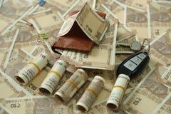Rolls indiska valutaanmärkningar, packe av valutaanmärkningar med plånboken, spridd indier 10 rupie valutaanmärkningar och biltan royaltyfri bild