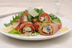 Rolls of jamon with blue cheese in lettuce leaves and parmesan Royalty Free Stock Photography