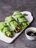 Rolls from lettuce leaf with vegetables and rice noodles and soy sauce with sesame. Vegetarian and vegan rolls with lettuce, carro. Ts, red cabbage, rice noodles stock photos